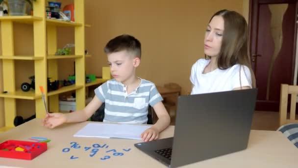 Mladá matka sedí u stolu doma a pomáhá svému synovi s domácím úkolem ze školy