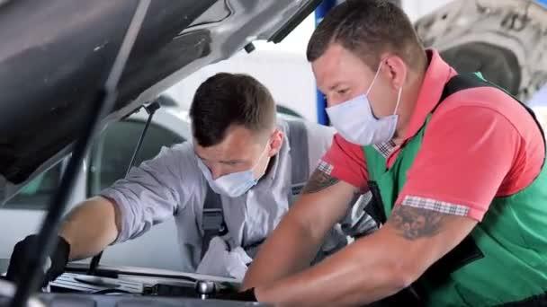 Automechanici s ochrannou maskou opravárenský vůz na čerpací stanici