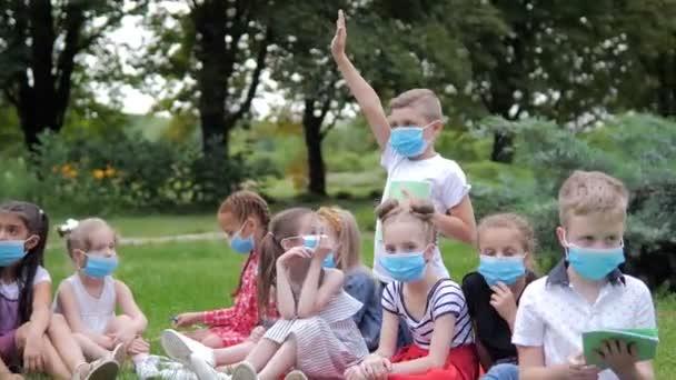 Egy tanár egy szabadtéri parkban tanít gyerekeket. Vissza az iskolába, tanulni a világjárvány idején