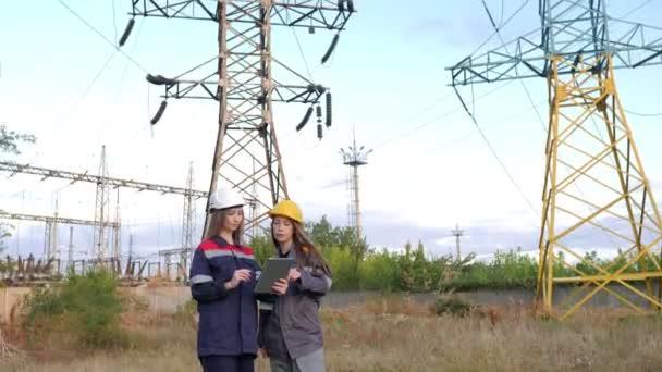 Dvě pracovnice v energetice provádějí kontrolu zařízení a vedení