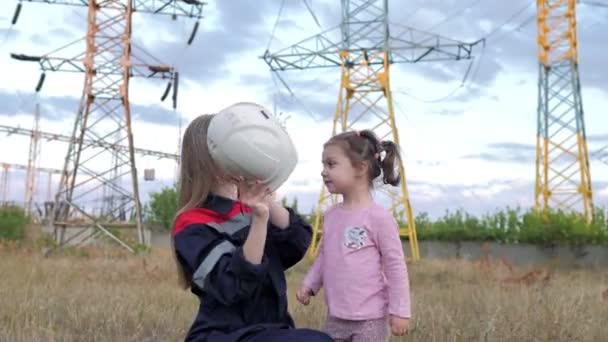 Mutter setzt ihrer Tochter einen Helm auf. Sorge um zukünftige Generationen und die Umwelt