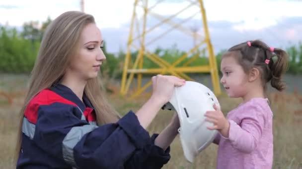 Ein kleines Mädchen setzt einem Techniker einen Helm für seine Mutter auf. Sorge um zukünftige Generationen und die Umwelt