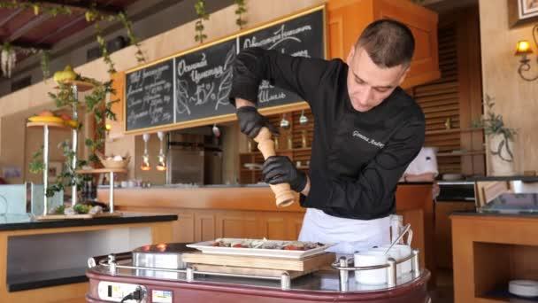 Kuchař v otevřené kuchyni vaří hovězí plátky na talíři s kořením