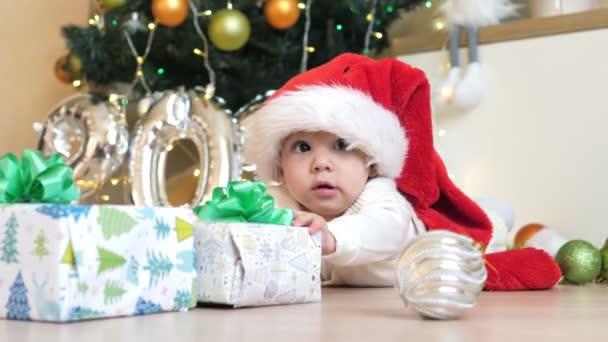 Portrét roztomilého novorozence v klobouku Santa, ležící na podlaze v pozadí vánočních dárků a stromu