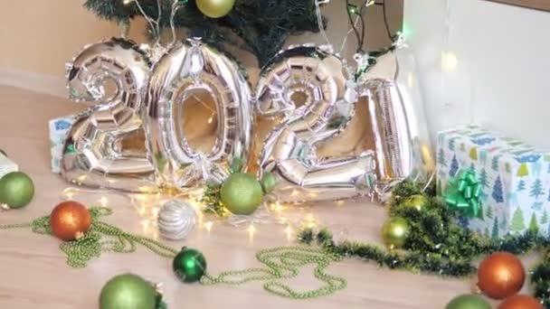 Újévi ünnepi összetétele 2021 ezüst lufik. Karácsonyfa a háttérben