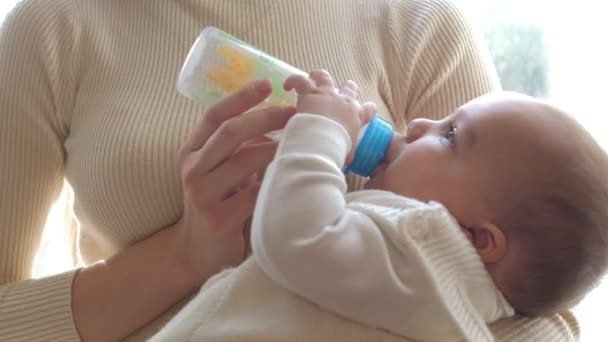 Closeup view of mother feeding her baby milk from bottle