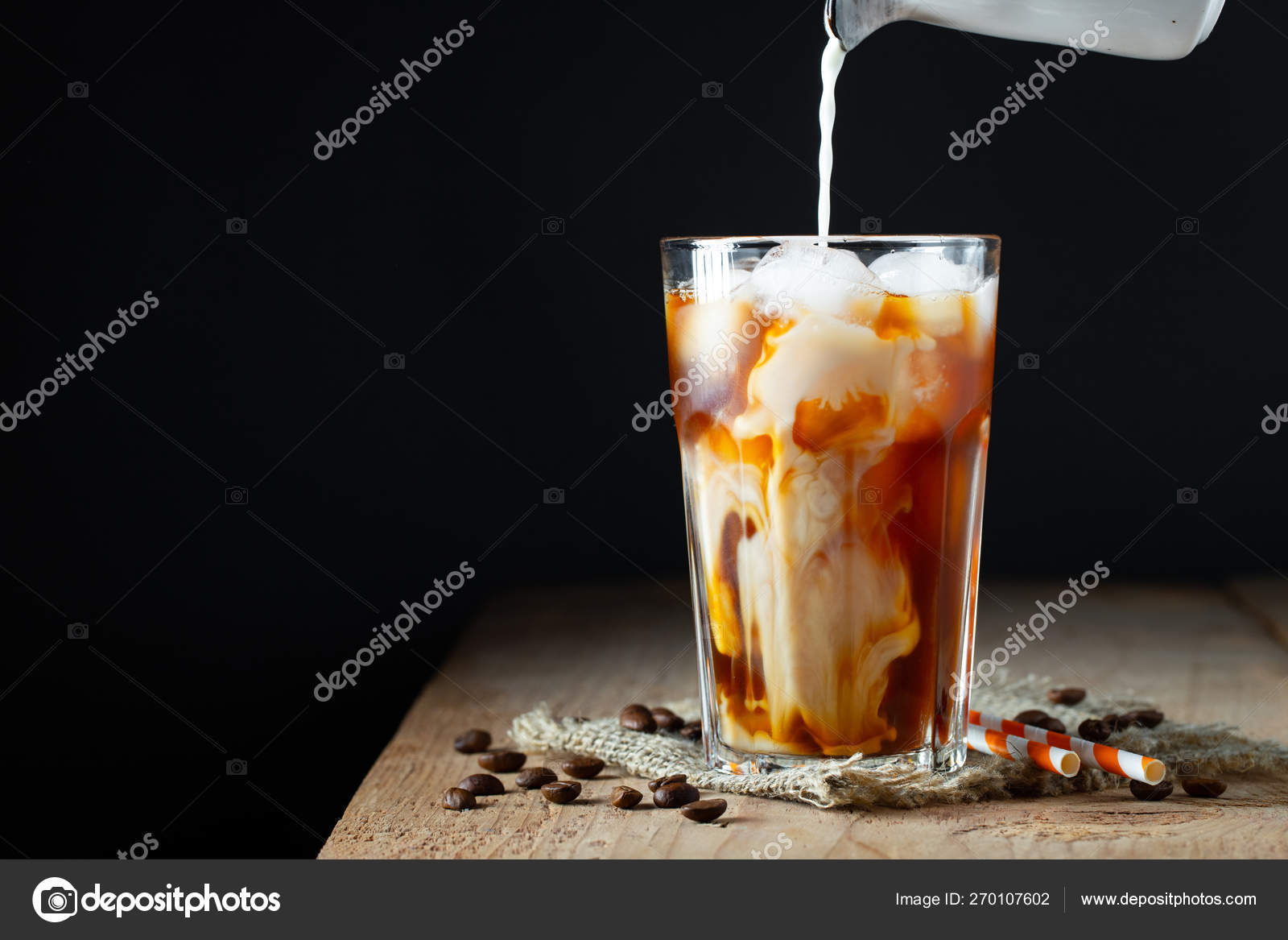 Кофе со льдом в высоком стакане со сливками, кубиками льда и бобами на старом деревенском деревянном столе. Холодный летний напиток с трубками на черном фоне с копировальным пространством — Стоковое фото ©