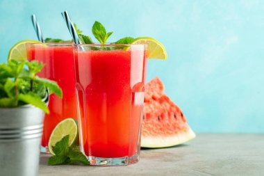 Watermelon slushie with lime and mint, summer refreshing drink in tall glasses on a light blue background. Sweet cold smoothie with copy space