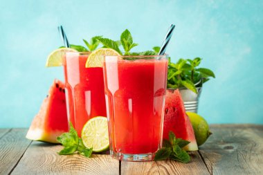 Watermelon slushie with lime and mint, summer refreshing drink in tall glasses on a light blue background. Sweet cold smoothie