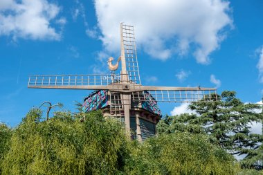 weather vane on old windmill qt blue sky background