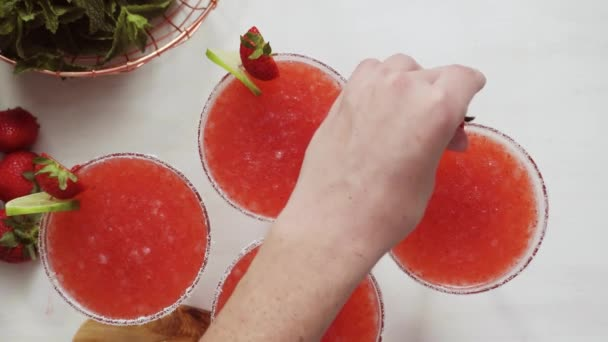 Step by step. Garnishing strawberry margarita with fresh lime and strawberries