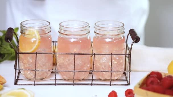 Step by step. Garnishing raspberry lemonade with fresh lemons and raspberries in drinking mason jars