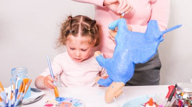 Mother and daughter painting paper mache unicorn with blue paint together.