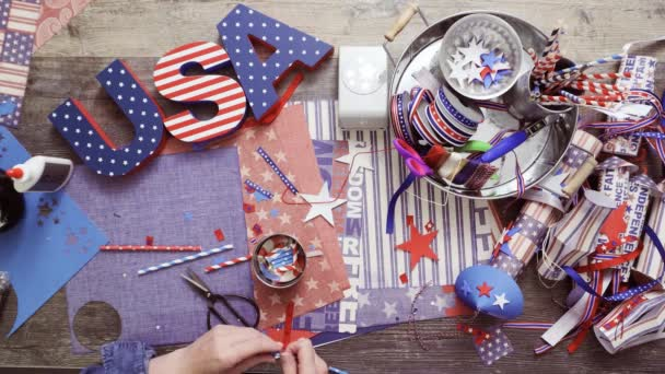 Step by step. Mother and daughter making neckles from paper straws and stars for July 4th celebration