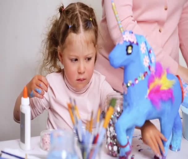 Step by step. Mother and daughter decorating paper mache unicorn with jewels and paper flowers