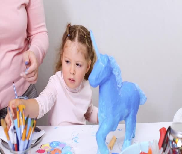 Step by step. Mother and daughter painting paper mache unicorn with blue paint together