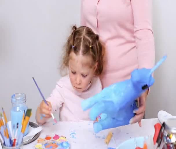 Time lapse. Step by step. Mother and daughter painting paper mache unicorn with blue paint together