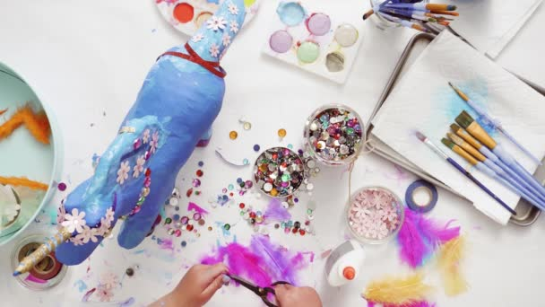 Step by step. Decorating painted paper mache unicorn with paper flowers and jewels