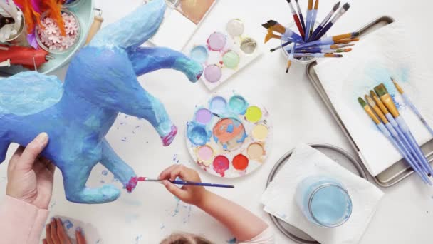 Step by step. Painting paper mache unicorn with blue paint