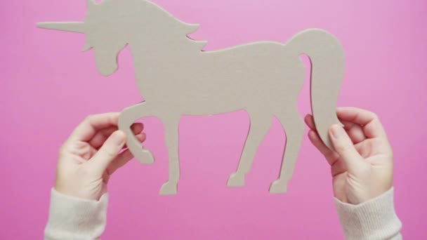 Unfinished unicorn cut out on pink background.