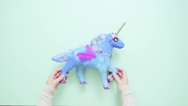 Kids craft. Painted blue and decorated with jewels and feathers paper mache unicorn.