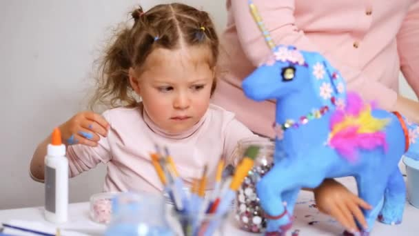 Step by step. Little girl decorating paper mache unicorn with jewels and paper flowers