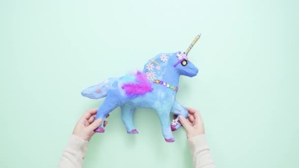 Kids craft. Painted blue and decorated with jewels and feathers paper mache unicorn