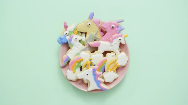 Unicorn shaped sugar cookies decorated with royal icing on pink plate