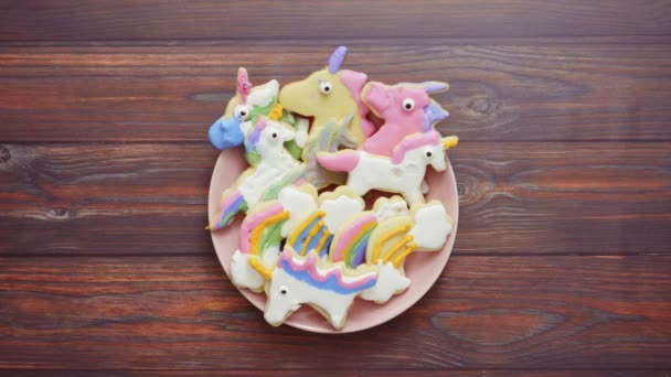 Unicorn shaped sugar cookies decorated with royal icing on pink plate.