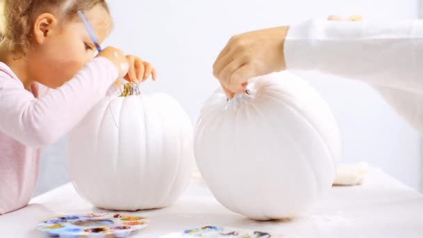 Step by step. Mother and daughter decorating Halloween craft pumpkin with unicorn theme