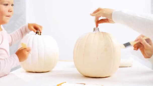 Time lapse. Step by step. Mother and daughter decorating Halloween craft pumpkin with unicorn theme