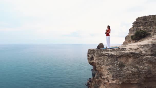 Woman standing and meditating on a cliff over the ocean. Yoga on the cliff.