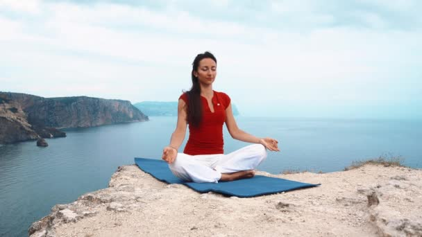 girl sitting on rock by sea, meditating in lotus yoga pose, concentrating, relaxing mind, soul and body