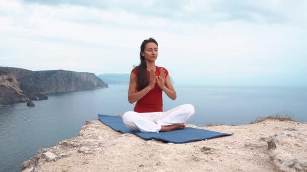 Mädchen sitzt auf Felsen am Meer, meditiert in Lotus-Yoga-Pose, konzentriert, entspannt Geist, Seele und Körper.