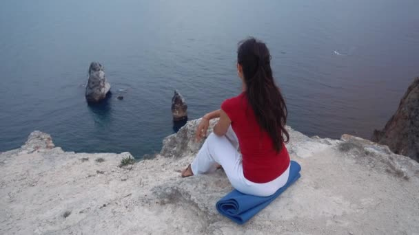 girl sitting on rock by sea, meditating in lotus yoga pose, concentrating, relaxing mind, soul and body.