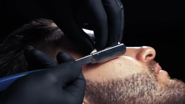 Close up of a handsome man getting his beard shaved in a hairdresser professional hairdresser using a razor shaving his customer profession.