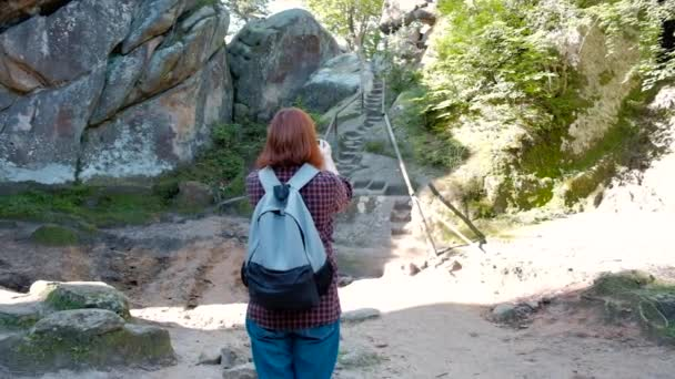 Slow motion portrait of girl traveller with knapsack taking pictures of beautiful view from cliff using smartphone.