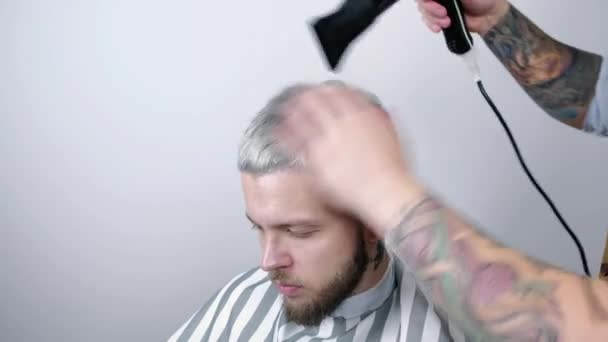 Mužské účes v salonu. Muž vlasy sušení v holičství. Holič účesu se sušičkou. Dokončete kadeřnictví. Vysoušeč vlasů muž v holičství