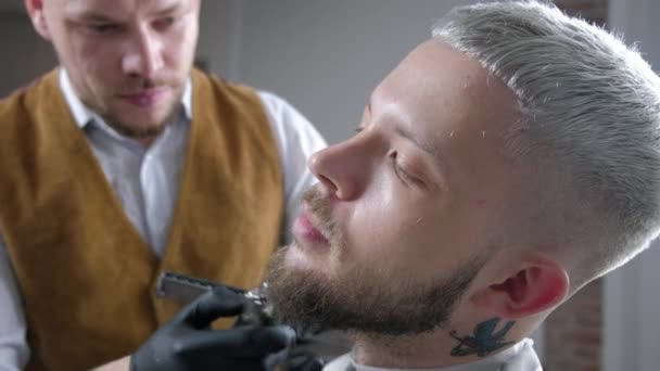 Shaving of beard. Barber cutting mens face hair with beard trimmer at barbershop.