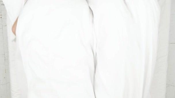 Mosolygó pár szórakozás a bed takaró alatt rejtőzik, és keres kamerába felülnézet.