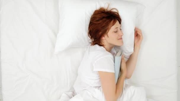 Žena v posteli s knihou o její ruku a spánku. pohled shora