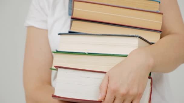 Studentka vysoké školy na kampusu univerzity drží mnoho knih v rukou