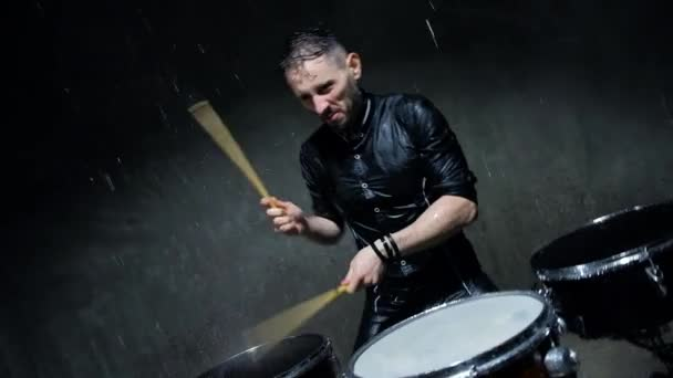 drummer playing drums with water in a dark studio