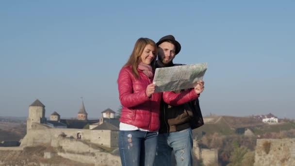 Mladí turisté místní brigádníky na starověké ulice pozadí, hledá nový cíl. Venku.