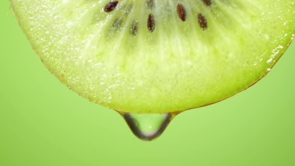 Close up or macro of a slice of kiwi, a drop of water falls in slow motion. The fruit gives off freshness and is filled with juice rich in vitamins and energy. Concept of fresh fruits, juices and kiwi