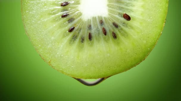 Close up or macro of a slice of kiwi, a drop of water falls in slow motion.