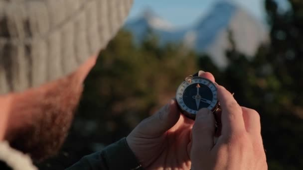 Close up on compass instrument in gloved hand . Mountain hiking trails. Fores trip concept.