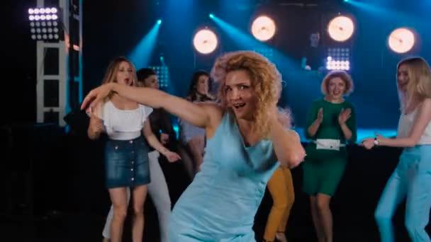 Göndör lány táncoló a buli Night Club. Vidám barátai a cég. Disco a kék árnyalatai, a modern ifjúsági élet. Lassított mozgás