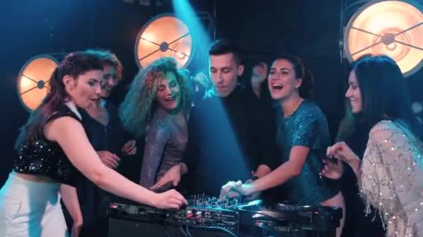 junge Frauen tanzen und flirten mit dem DJ in einem Nachtclub