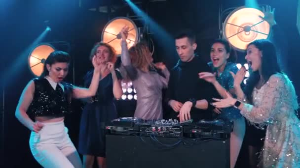 Mladé ženy tančí a flirtují s DJ v nočním klubu